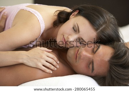 Young Couple Relaxing On Bed - stock photo