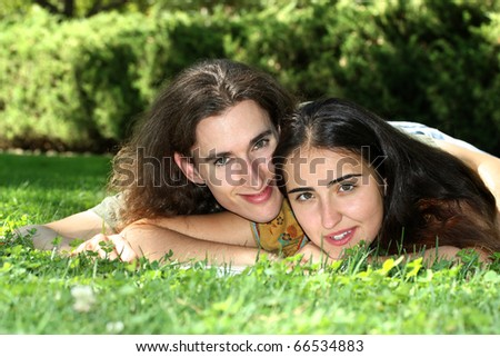 Young couple relaxing on college campus - stock photo