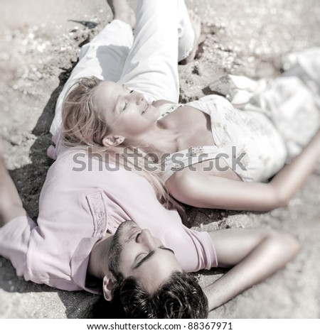 Young couple relaxing on sand at beach and daydreaming with their eyes closed