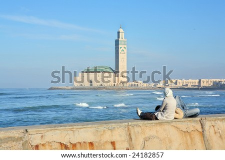 Young couple relaxing on seafront with view of Mosque of Hassan II in Casablanca, Morocco - stock photo