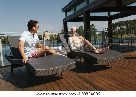 Young couple relaxing on sunbeds - stock photo
