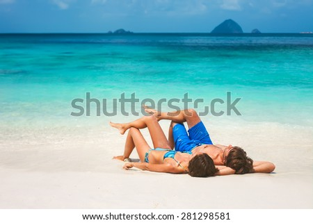 Young couple relaxing on the beach - stock photo