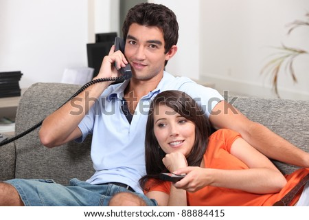 Young couple relaxing on the couch, talking on the telephone and watching television
