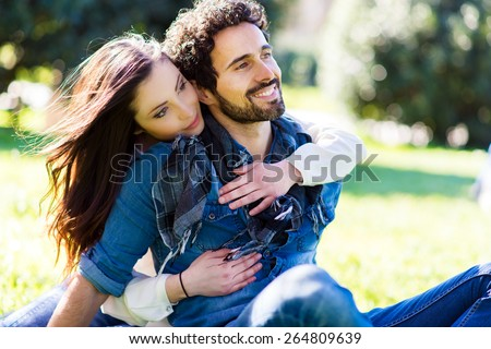 Young couple relaxing on the grass in the park - stock photo