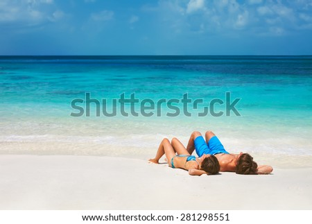 Young couple relaxing on the tropical beach - stock photo