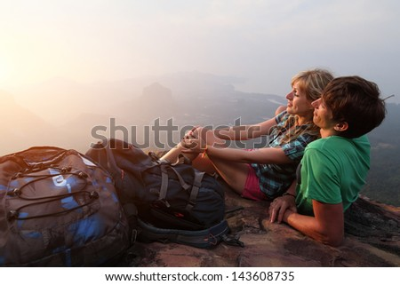 Young couple relaxing on top of a mountain and enjoying sunrise - stock photo