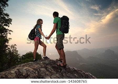 Young couple relaxing on top of a mountain and enjoying sunrise