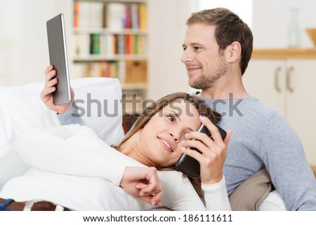 Young couple relaxing together on the sofa as he reads an e-book on his tablet and she consults a text message on her smart phone - stock photo