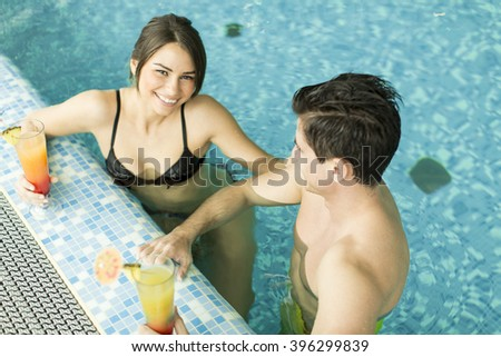 Young couple relaxing with drinks in the pool