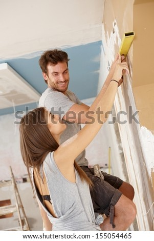 Young couple renewing house, measuring, DIY. - stock photo