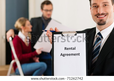 Young couple renting a home or apartment, they are meeting the owner or real estate broker standing in front - stock photo