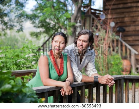 Young couple resting at a small bridge in a garden. Shallow DOF, focus on girl's face. - stock photo