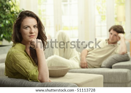 Young couple resting at home lying o couch. Selective focus on woman. - stock photo