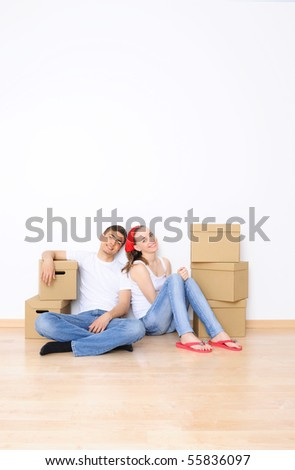 Young couple resting from moving into a new home. Great copy space. - stock photo