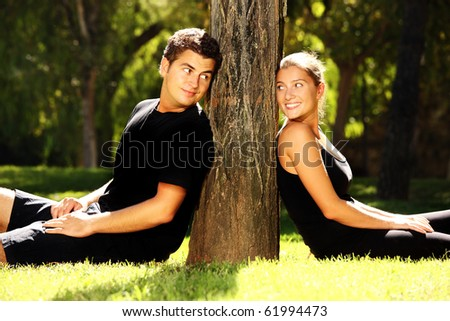 Young couple resting in the park near the tree