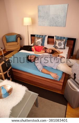 Young couple resting on bed in hotel room upon arrival. Luggages around. - stock photo