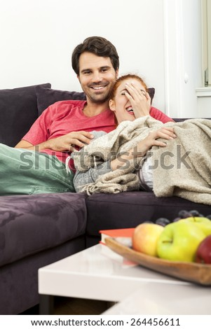 Young Couple Resting on the Sofa at the Living Room While the Man is Watching TV and Woman is Reading a Book. - stock photo