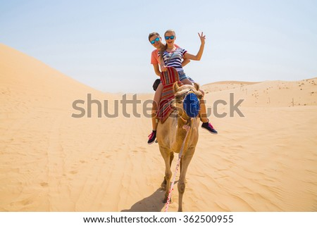 Young couple riding a camel in the middle of a desert near Emirates on their wedding day - stock photo