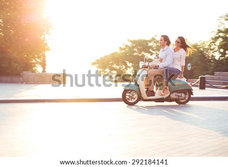 Young couple riding a scooter and having fun. Sun is shining in the morning - stock photo
