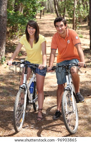 Young couple riding bikes in a forest - stock photo