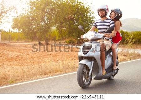 Young Couple Riding Motor Scooter Along Country Road - stock photo