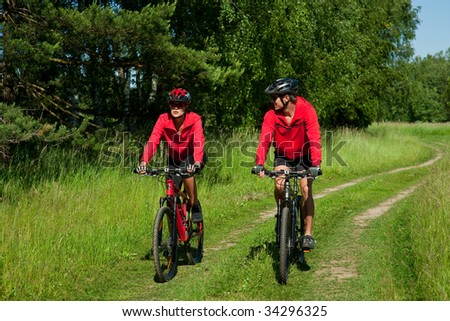 Young couple riding mountain bike  and wearing red clothes