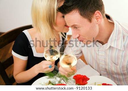 Young couple romantic dinner: both holding white whine glasses, she is whispering something; focus on his face - stock photo