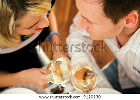 Young couple romantic dinner: clinking the white wine glasses; focus on the eyes of the people