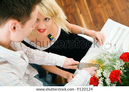 Young couple romantic dinner: he is grating cheese over her pasta; focus on face of the girl - stock photo