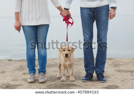 Young couple running along the beach with their dog. Young couple walking on the beach of the lake or river with a puppy, small dog Labrador. Cloudy autumn, dressed in sweaters and pullovers - stock photo