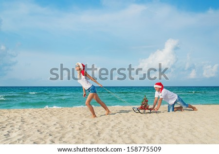 Young couple running at sea beach in red santa hats with color sled and decorated christmas tree - holiday concept