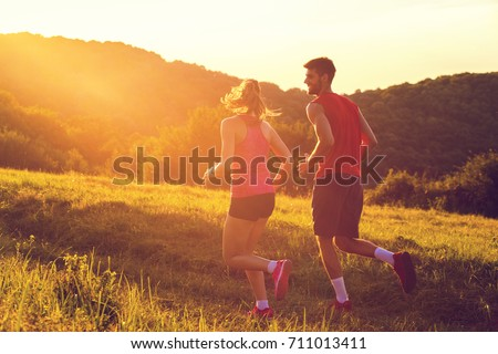 Couple running in sunset