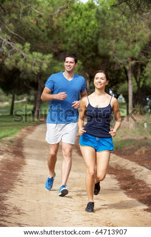 Young couple running in park - stock photo