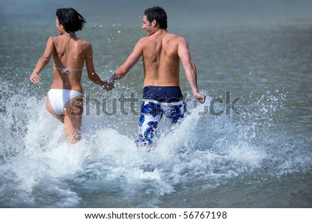 Young couple running in the sea