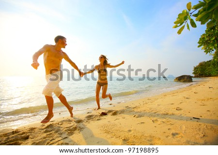 Young couple running on a tropical beach at sunset - stock photo