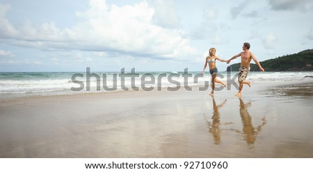 Young couple running on a wet beach - stock photo