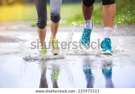 Young couple running on asphalt sports field in rainy weather. Details of legs and sports shoes splashing in puddles. - stock photo