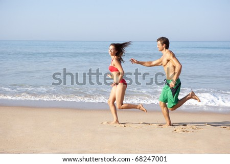 Young couple running on beach - stock photo