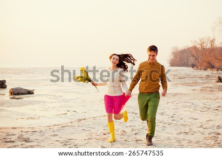 young couple running on the beach - stock photo