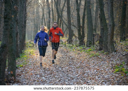 Young Couple Running on the Trail in the Wild Forest. Active Lifestyle - stock photo