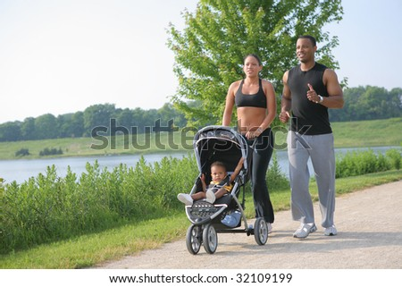Young Couple Running Outdoor with Little Boy in Stroller Under Morning Sun Light