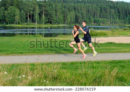 Young couple running outside - stock photo