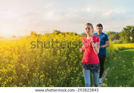 Young couple running outside in spring canola field - stock photo