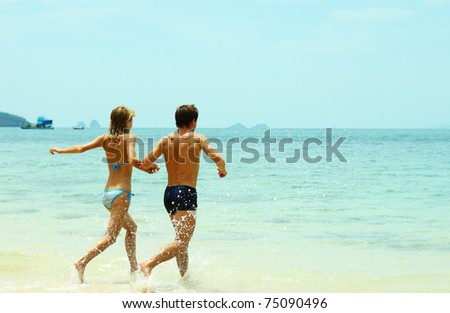 Young couple running to the blue sea - stock photo