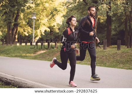 Young couple running together in park - stock photo