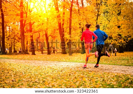 Young couple running together in park - fall nature - stock photo