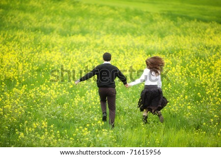 Young couple running together on a green and yellow field. - stock photo