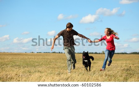Young couple running together on meadow with dog - stock photo