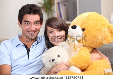 Young couple sat with giant teddy bear - stock photo