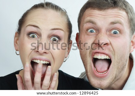 young couple screaming into the camera. couple portrait. - stock photo